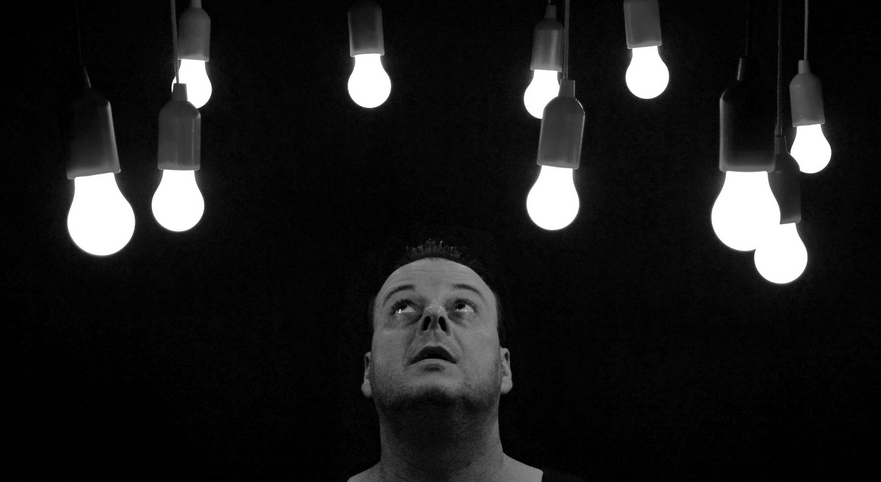 man looking above light bulbs grayscale